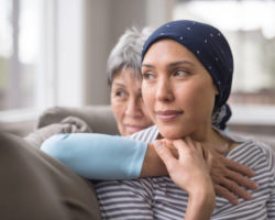 An ethnic woman wearing a headscarf and fighting cancer sits on the couch with her mother. She is in the foreground and her mom is behind her, with her arm wrapped around in an embrace, and they're both looking out the window in a quiet moment of contemplation.