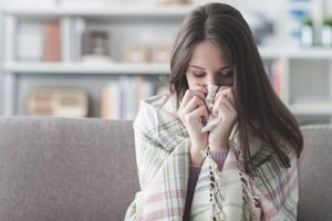 Sick young woman at home on the sofa with a cold, she is covering with a blanket and blowing her nose